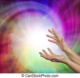 Pair of female hands outstretched into a whirling vortex of colorful light and energy