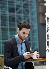 Sending text message on mobile phone - Portrait of a young...
