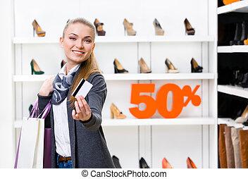 senhora, mostrando, cartão crédito, em, calçado, loja