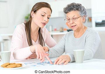 senhora velha, fazendo, um, quebra-cabeça