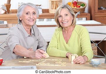 senhoras, aposentado, duo, scrabble, tocando, cozinha