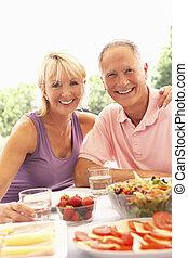senior összekapcsol, eszik outdoors