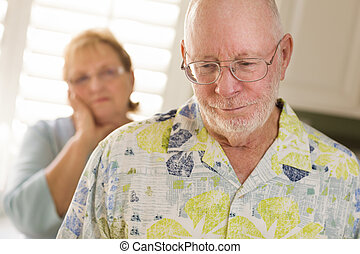 Senior Adult Couple in Dispute or Consoling in Kitchen of...