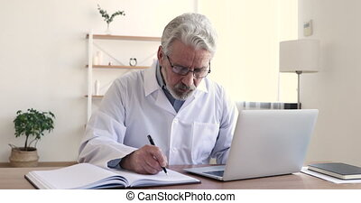 Serious older 60s male professional physician wearing white lab coat and glasses writing prescription notes using laptop computer. Senior adult doctor working alone sitting at desk in medical office.