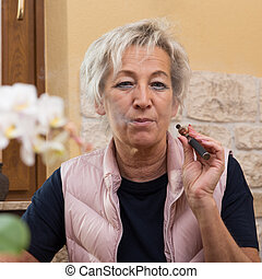 senior adult with e cigarette - senior adult woman with...