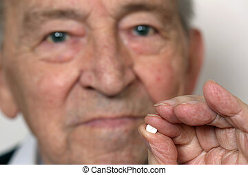Senior adult with medicine pill - Senior adult holding a...