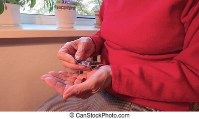 Senior adult woman holding painkiller pills on female hand pouring two capsules from meds bottle taking medicine, old elderly grandmother health care, pharmacy and treatment concept, close up view