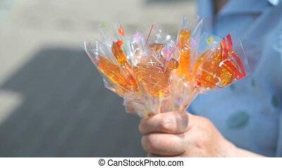 Senior adult woman selling homemade lollipops - Senior adult...