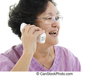 Senior adult woman talking on phone - Portrait of 60s Asian...