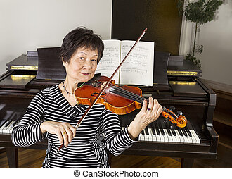 Senior Adult Women Playing the Violin - Senior adult woman...