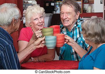 Joyful group of senior adults toasting with coffee mugs