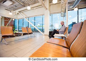 senior, affärsman, användande laptop, in, flygplats, påtryckningsgrupp