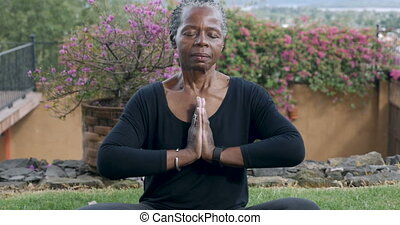 Senior African American woman finishing her yoga routine with a namaste