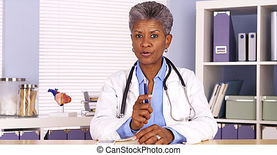 Senior african doctor sitting at desk and talking to camera
