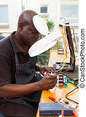 senior african technician repairing circuit board