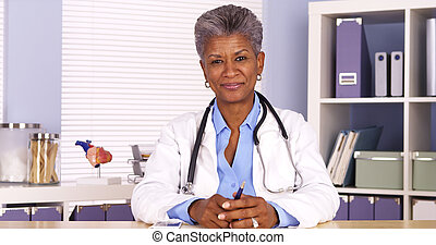 Senior African woman doctor sitting at desk and talking to camera