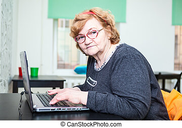 Senior age woman sitting at table with laptop on table, looking at camera