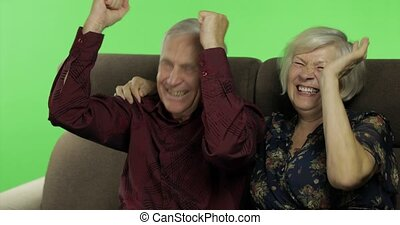 Senior aged man and woman sitting together on a sofa and watching TV. Chroma key