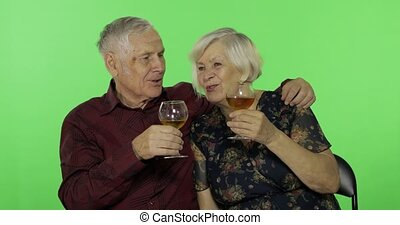 Senior aged man drinking white wine with a elderly woman ...