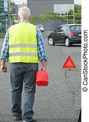 senior aged man holding gas can to refill his car