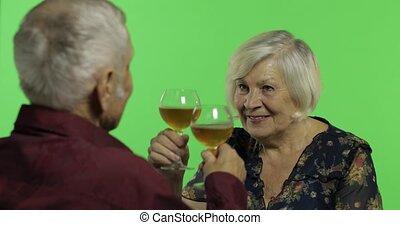 Senior aged woman drinking wine with a elderly man companion...