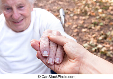 Senior and young woman holding hands
