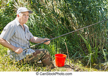 Senior angler fishing from a reed bank