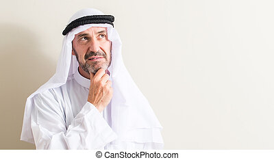 Senior arabic man serious face thinking about question, very confused idea