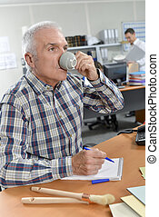 Senior architect drinking coffee at his desk