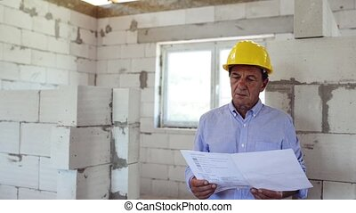 Senior architect or civil engineer at the construction site....
