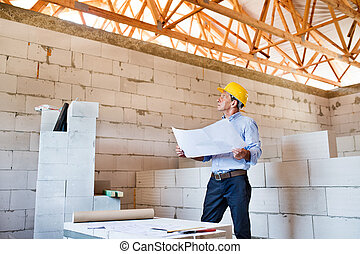 Senior architect or civil engineer at the construction site.