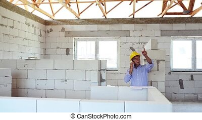 Senior architect with smartphone at the construction site. -...