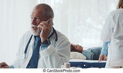 senior, arts, met, smartphone, in, zijn, kantoor.