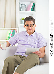 senior asian chinese enjoying on a sofa in home