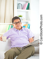 senior asian chinese  reading newspaper on a sofa in home