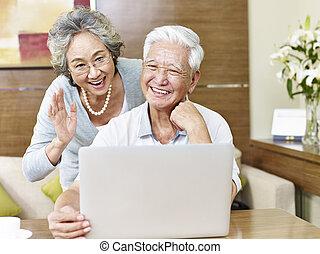 senior asian couple chatting online