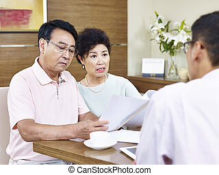 senior asian couple shocked by a salesman
