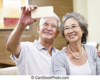 senior asian couple taking a selfie