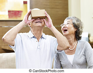 senior asian couple trying vr device