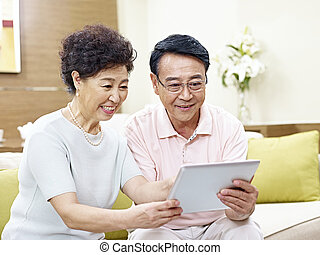 senior asian couple using tablet computer together