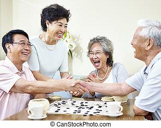 senior asian people playing weiqi - senior asian men shaking...