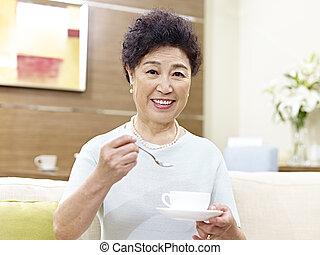 senior asian woman drinking coffee