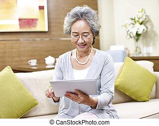 senior asian woman using tablet computer