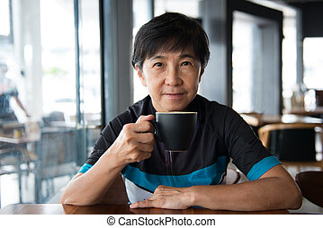 Senior Asian woman with coffee in cycling jersey