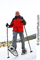 Senior at the snow-shoe walking in winter - Older man in...