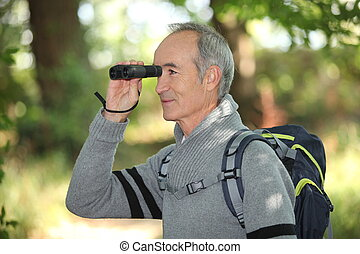 Senior backpacker looking through binoculars