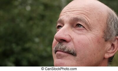 Senior bald man with mustache looking fixedly up. Close up...