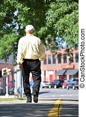 Senior Balding Male Walking On Sidewalk