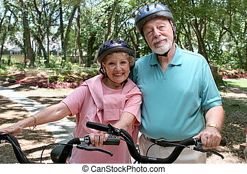 Senior Bikers - An attractive senior couple bicycling...