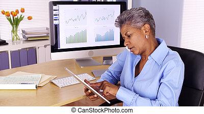 senior, black , businesswoman, klesten, op, smartphone, en, gebruik, tablet
